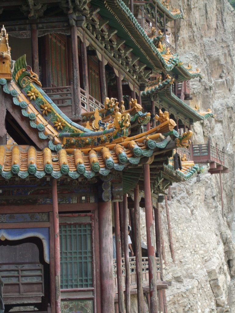 The sweeping corner of a colorful roof, with carvings along the crest.