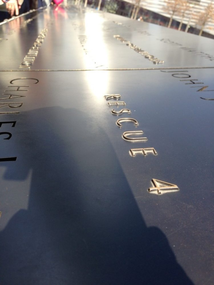 a detail of the 9/11 memorial in New York City: a dark shiny marble wall with raised letters spelling out the victims' names and their affiliations.