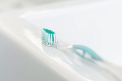 A toothbrush lies on the edge of a sink.