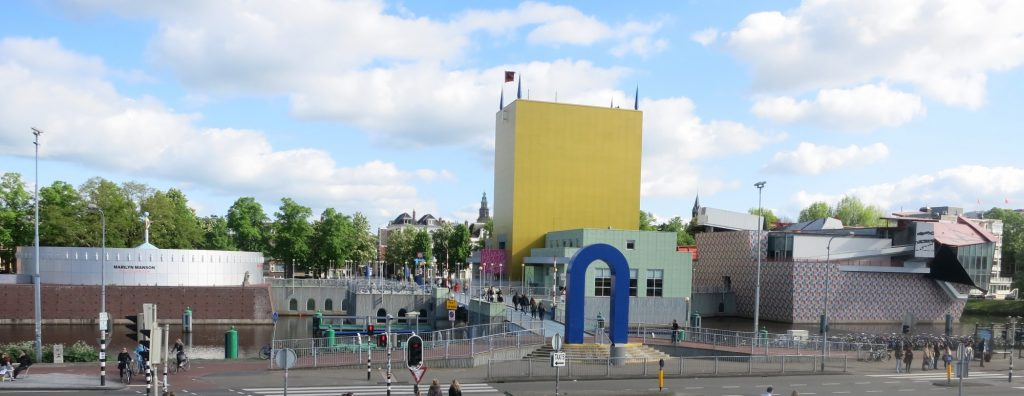 An upside-down U forms the entrance. Beyond that, a bridge, then parts of the museum on the left and right. On the right, a tall yellow building with no windows. Also a smaller light green building. Further right, a building that is very oddly shapped, with part of it sticking out at an angle. On the left of the bridge is a low, round, grey building.