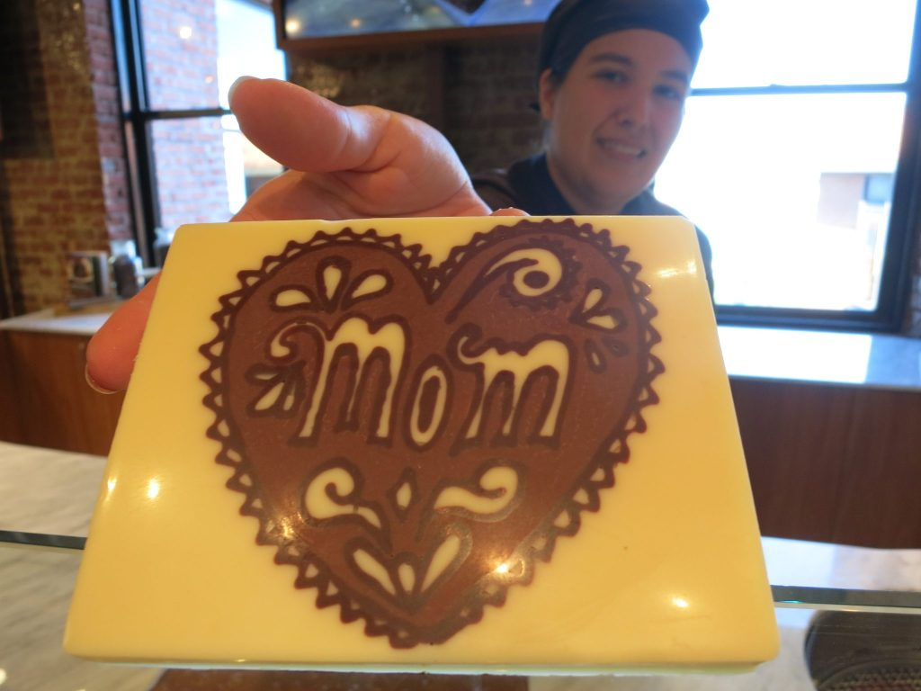 "Jessica holding a chocolate slab with ""mom"" drawn on it."