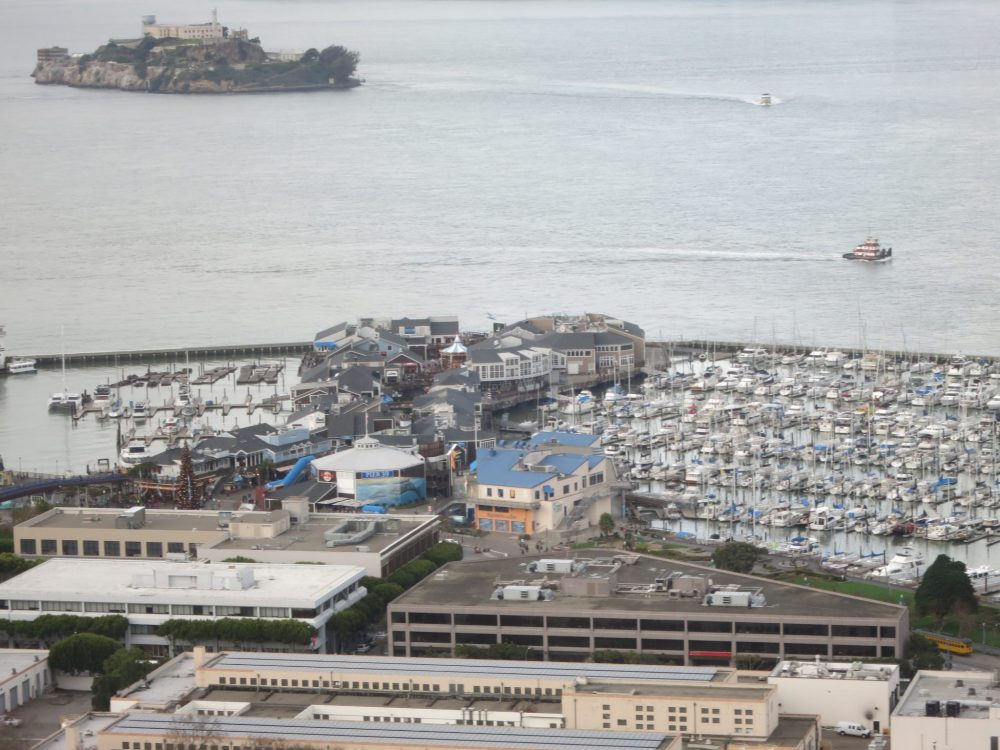 view of Fisherman's Wharf: the wharf is covered with buildings. ON the left and the right of it are harbors. The one on the left is mostly empty while the one on the right is crowded with boats. Open water beyond that, with Alcatraz Island at the top of the picture.