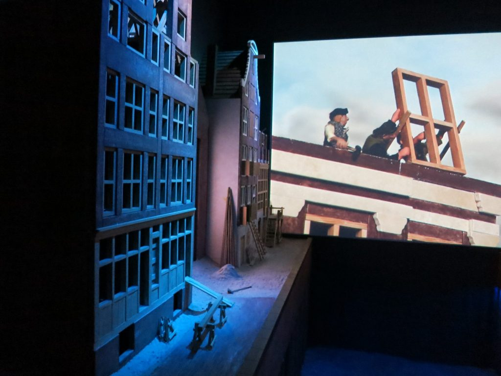 On the left are blue-lit model houses and on the far wall a piece of a film is visible. Canal House Museum Amsterdam