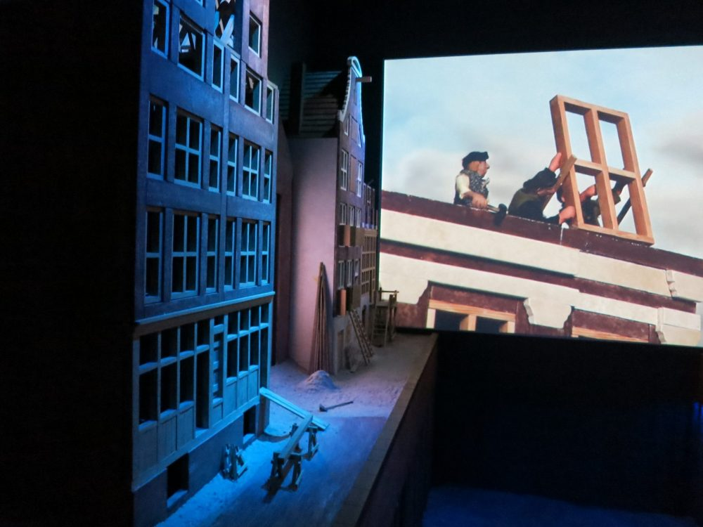 On the left are blue-lit model houses and on the far wall a piece of a film is visible showing workers installing a window frame. Canal House Museum Amsterdam