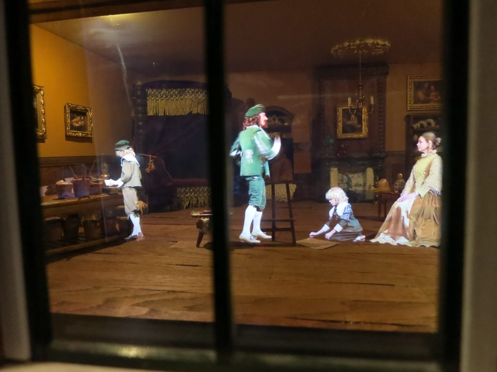 The painter wears knickers and a beret, while a woman poses with a child on the floor in front of her. At the Canal House Museum in Amsterdam.