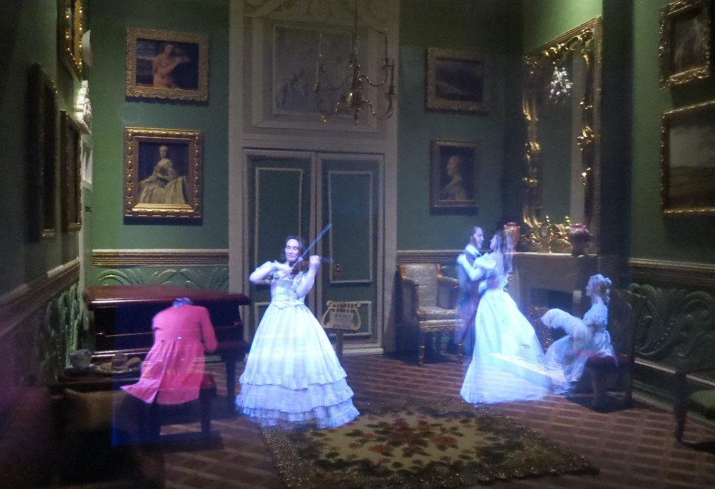 In an elegant room lined with portraits, a woman plays guitar in a long white dress, a man in a red coat plays piano, and several other people dance.