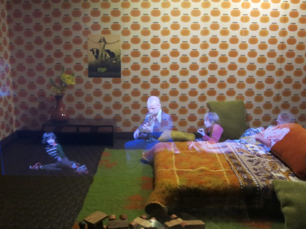 sitting on the floor, a man in a 60's era room plays guitar for his children. At the Canal House Museum in Amsterdam