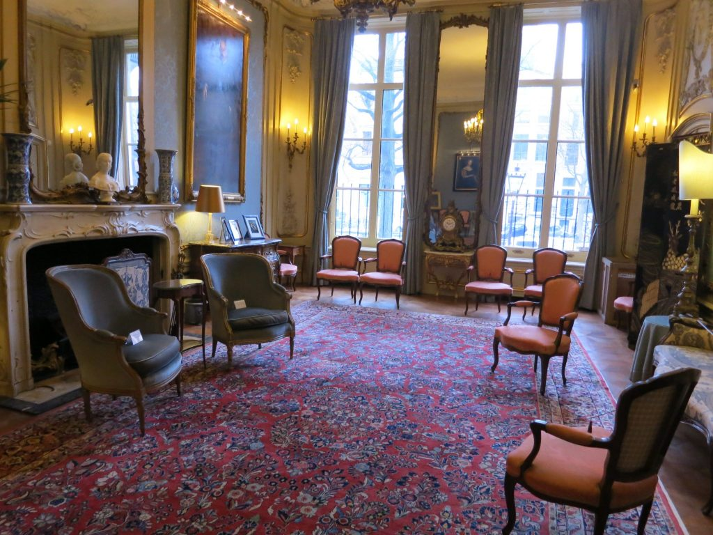 An elegant drawing room with dark carpet and a scattering of chairs at the Museum van Loon.
