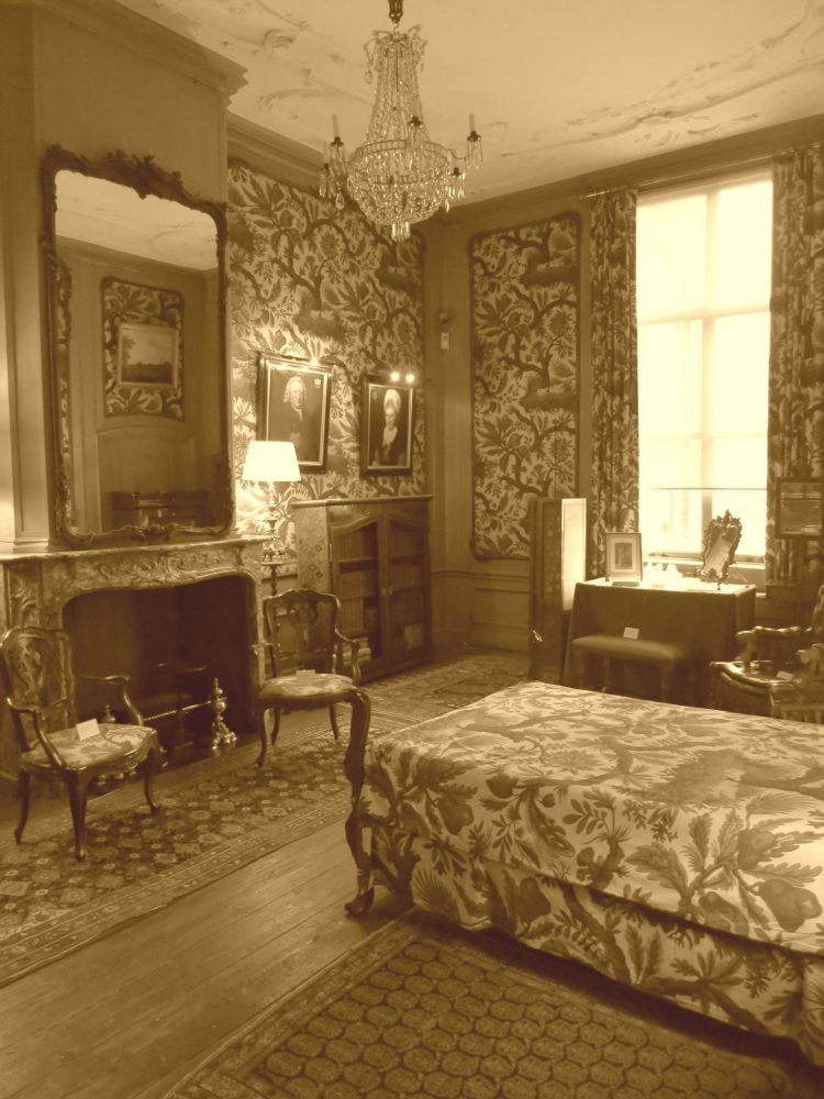 An elegant bedroom in the van Loon Museum. The bedspread, framed sections of wallpaper and the curtans all have a flowery, paisley pattern. A crystal chandelier hangs from the ceiling and the mantel has a huge mirror over it.