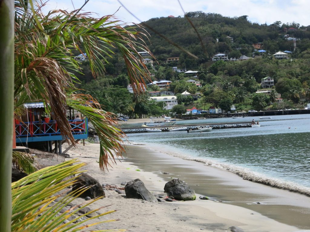 "a view down the beach, taking from the restaurant used in the filming of ""Death in Paradise"""