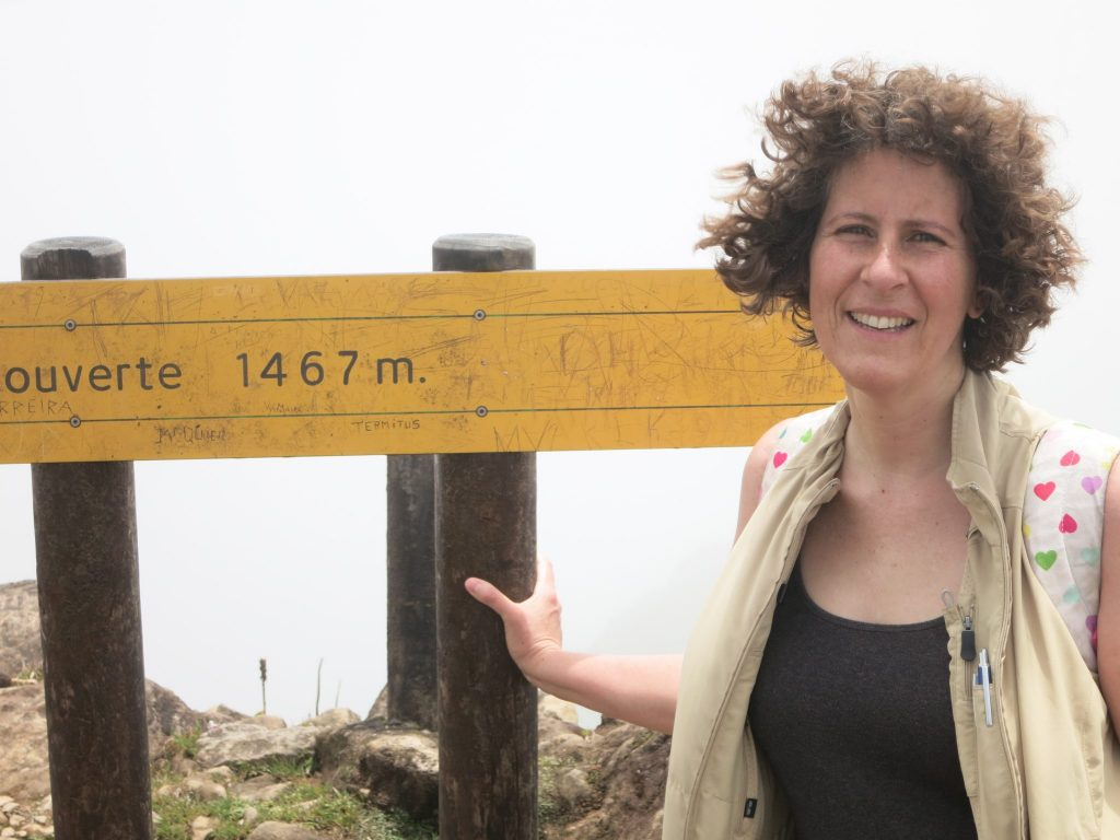 """picture of me at the top of La Soufriere volcano: My hair, curly at the time, is standing straight out from my head. I'm wearing a black t-shirt and a beige travel vest, and the straps of a backpack are visible on my shoulders. Behind me is a sign reading """"1467 m."""". Behind that, nothing but cloud."""