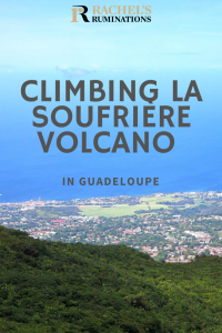 Pinnable image Text: Climbing La Soufriere Volcano in Guadeloupe Image: a view down over land and villages far below and the very blue sea beyond, blending with the blue sky.