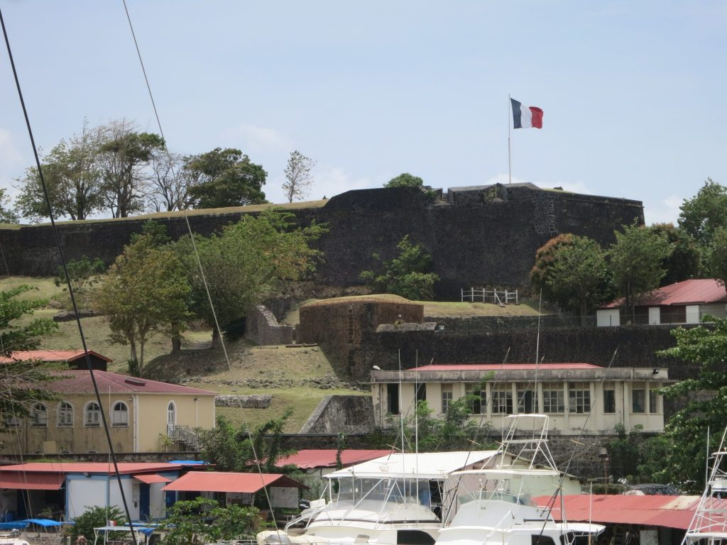 boats in the foreground, the wall of Fort St. Louis with a French flag in the background