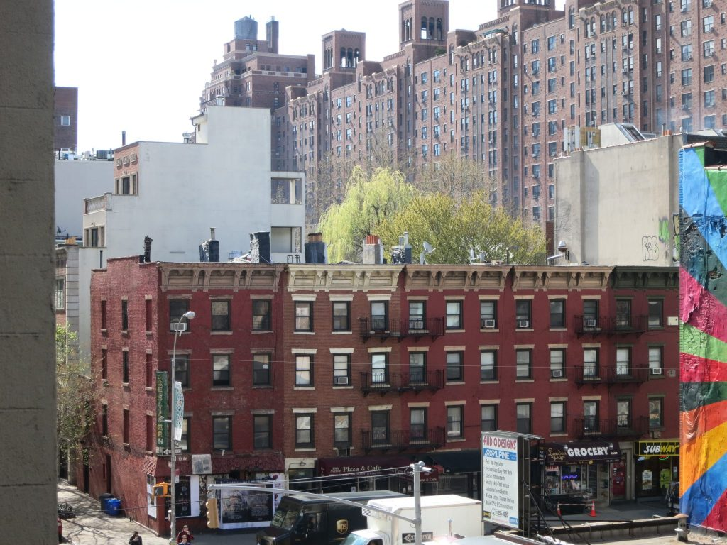 view from the High Line of small rowhouse buildings backed by huge apartment buildings