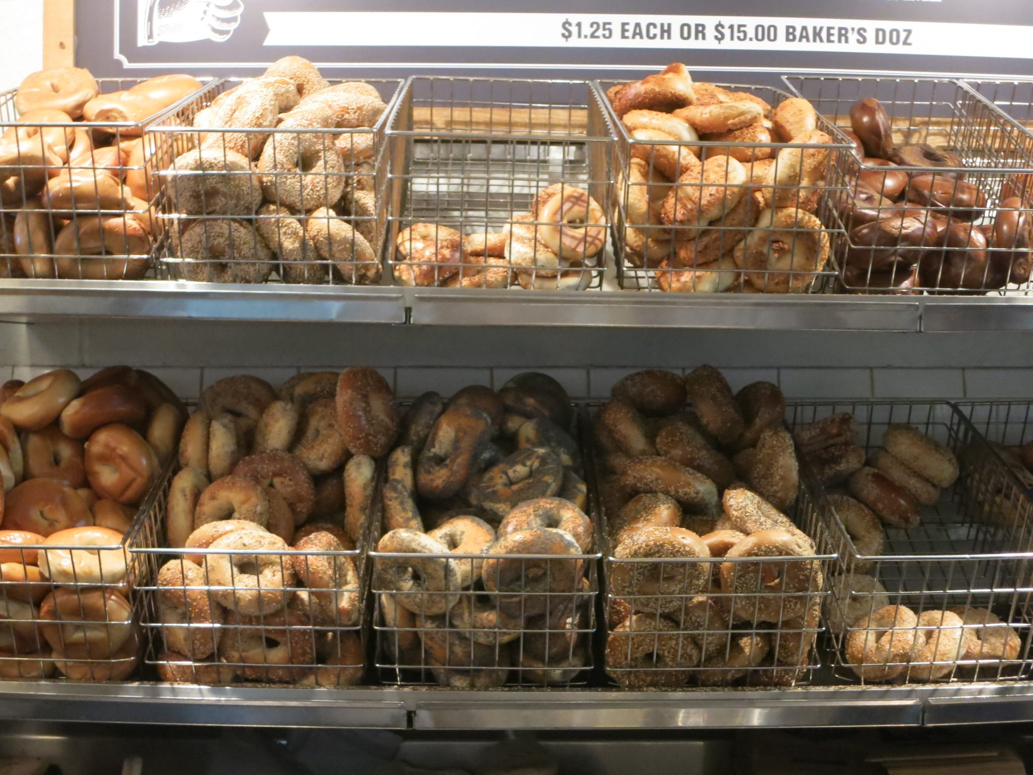 Lots of different types of bagels, displayed in baskets in a bagel store