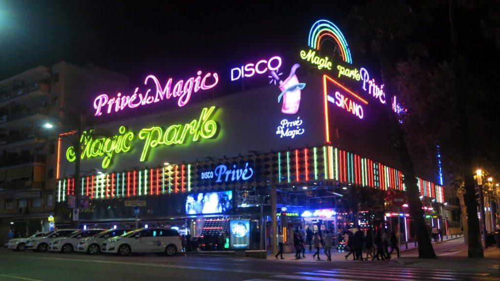 building in Lloret de Mar with neon-lighted signs reading Prive de Magic Disco, Magic Park, etc.