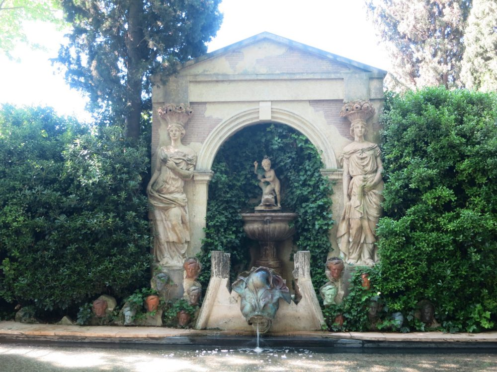 While the main structure of the fountain includes two classically-posed female statues in the garden of the Gala Dali museum, the fountain below is flanked by a number of small, identical carvings of heads: Wagner's face, repeated.