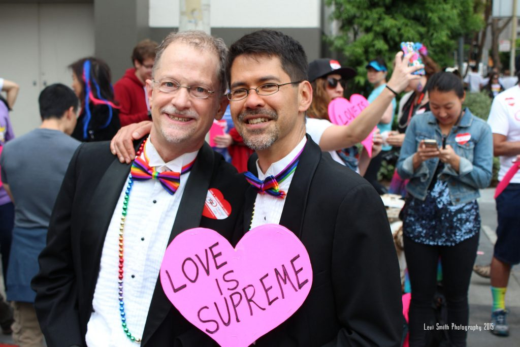 John Lewis and Stuart Gaffney, wearing tuxes with rainbow-colored bow ties, carrying a sign reading