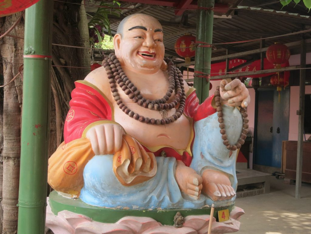 a laughing figure at a shrine on Pulau Ubin. A fat man, presumably meant to be Buddha, sits with on leg bent to the side and the other knee bent upward. Hi wears pale blue loose pants and a red robe, but the robe is open at the front, showing his belly, and it exposes his shoulders as well. He has several necklaces around his neck and one on his hand, all made of something round and brown, perhaps nuts of some sort. He has a big smile on his face.