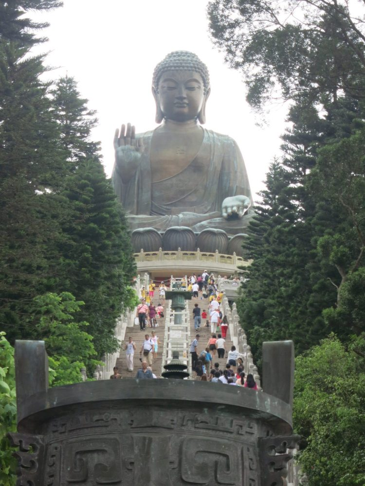 view up the stairs with the Big Buddha at the top. The people on the long stairway are not even as tall as the Buddha's fingers. The Buddha sits cross-legged, with one hand flat, palm turned up, and one hand raised, palm turned forward. His eyes are shut.