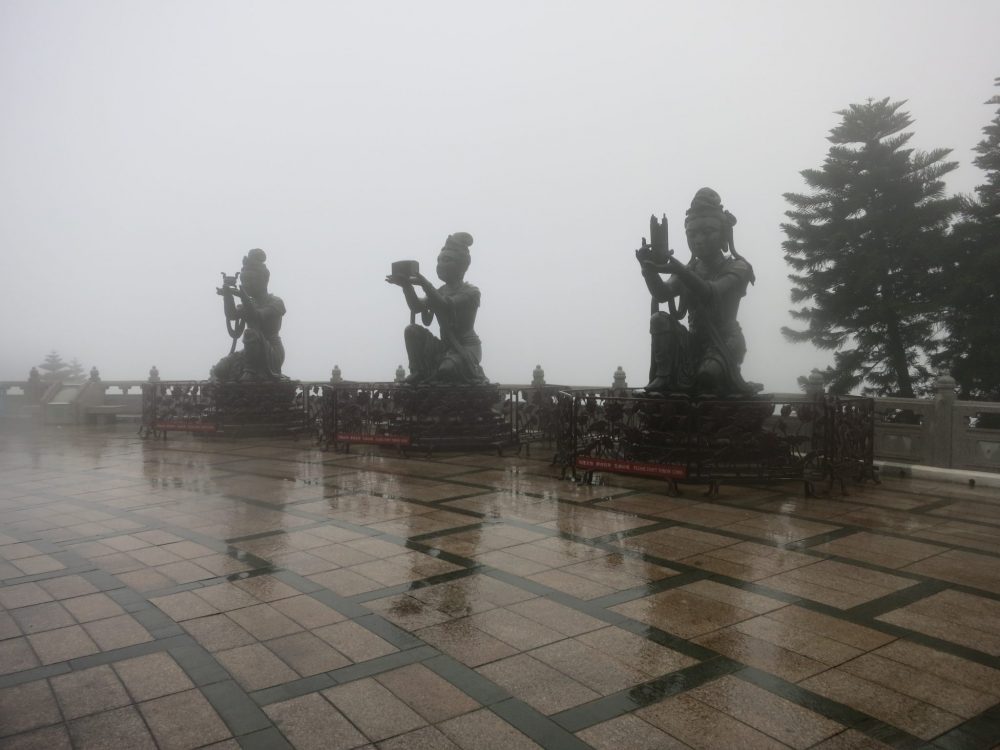 Three of the Deva statues, making offerings to the Buddha above. It was raining hard when the photo was taken, so the three statues are rather fuzzy. Each kneels and holds something up in both hands as an offering.