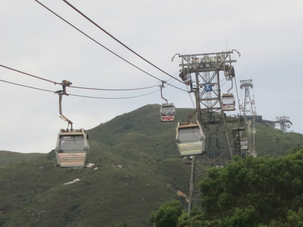 view of the cable car line from the end near the Big Buddha. The wires curve down between each of the supporting towers, with the small cars hanging from the wires: square boxes with windows. The landscape is green and mountainous.
