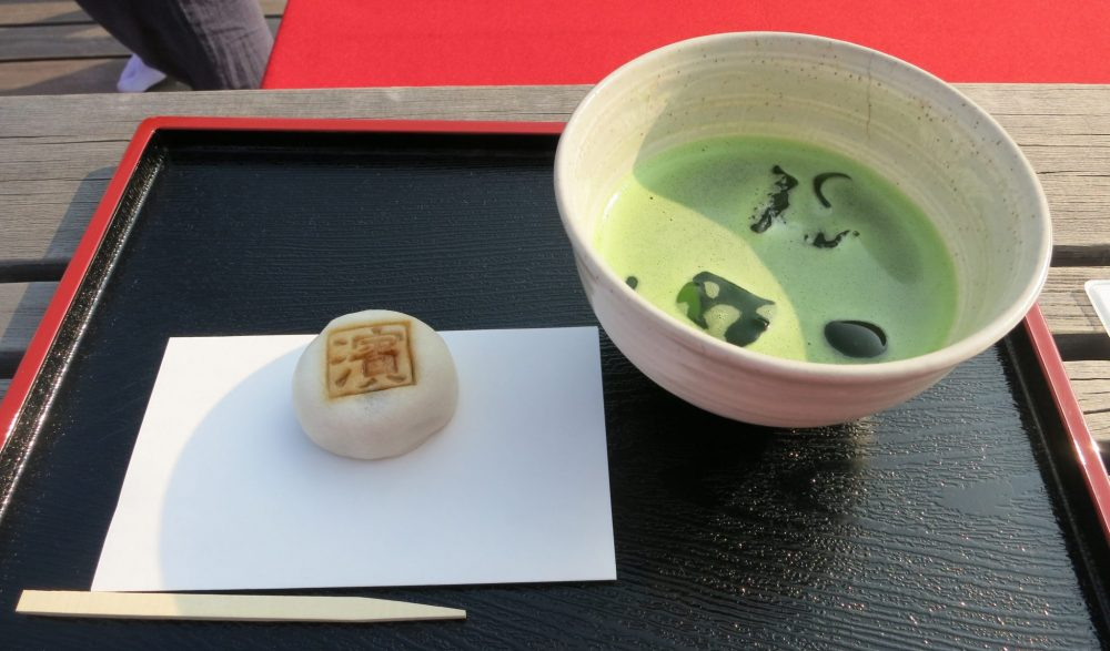 a bowl of green tea and a small sweet in the teahouse of Hama-rikyu Garden in Tokyo