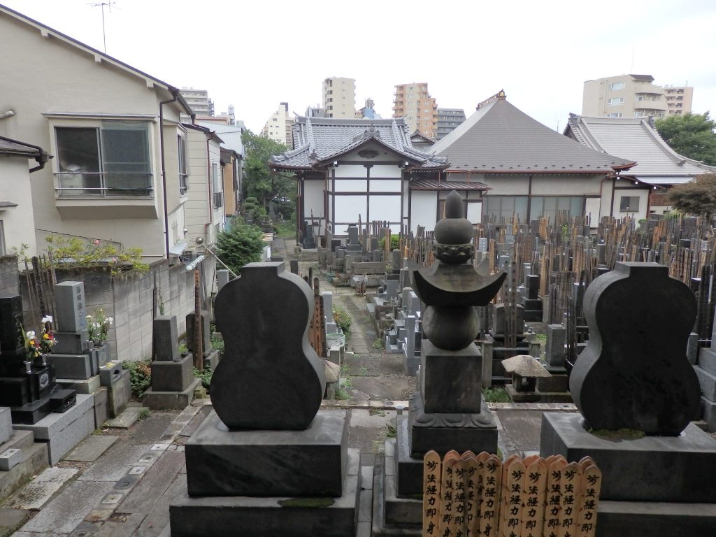 a crowded graveyard with the back of a temple in the background, in Yanaka, Tokyo
