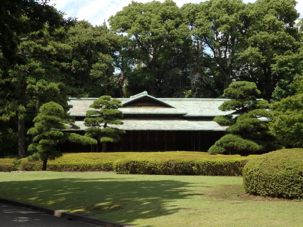 neatly pruned shrubbery and trees surround a low building in the Imperial Garden East in Tokyo