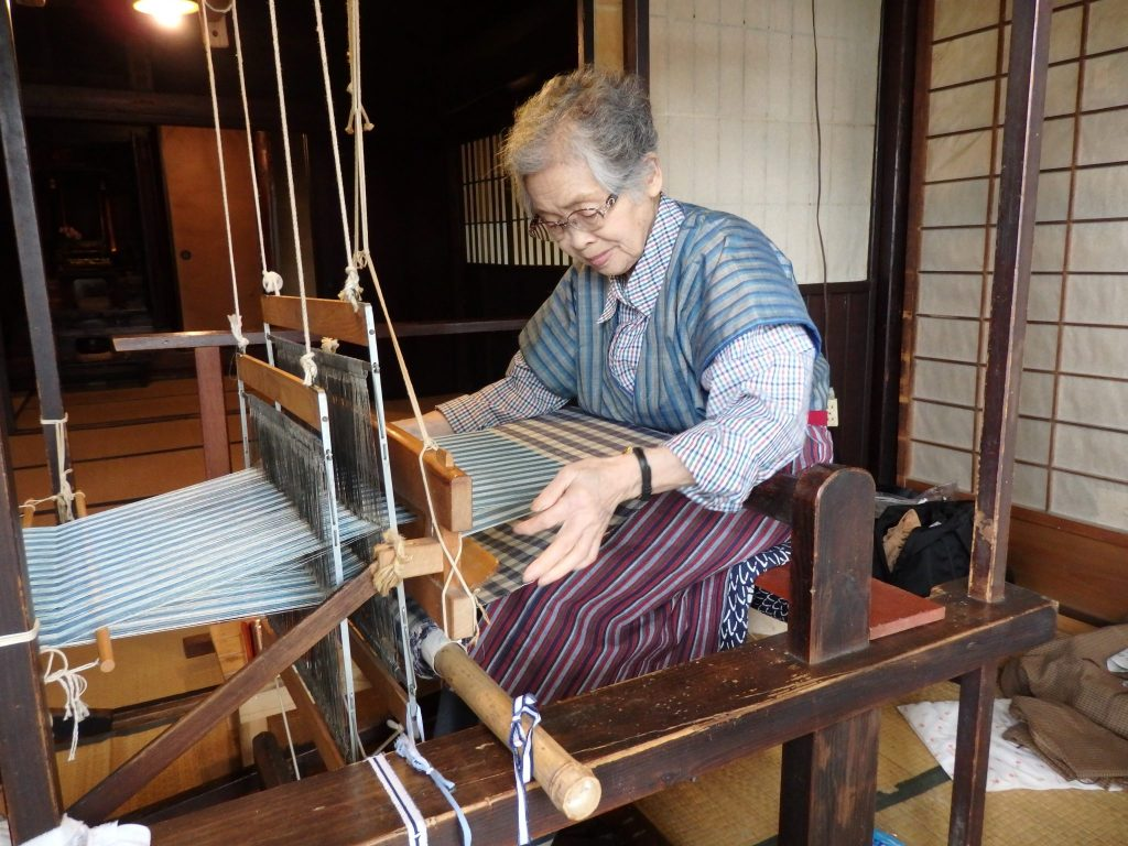 a woman operating a loom in one of the houses in Hida Folk Village, Takayama, Japan