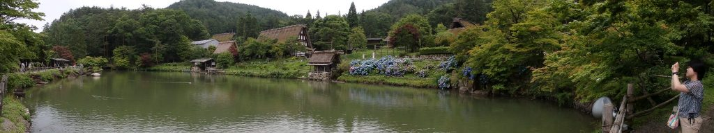 a pond, with a few houses and a mill next to it, at Hida Folk Village