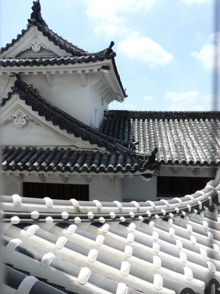 roof detail on Himeji Castle: behind is a grey roof, with rounded tiles in lines, the gables of the roof curved. Nearby a small part of a white roof is visible, again with curved tiles, but also with regular decorative crosspieces.