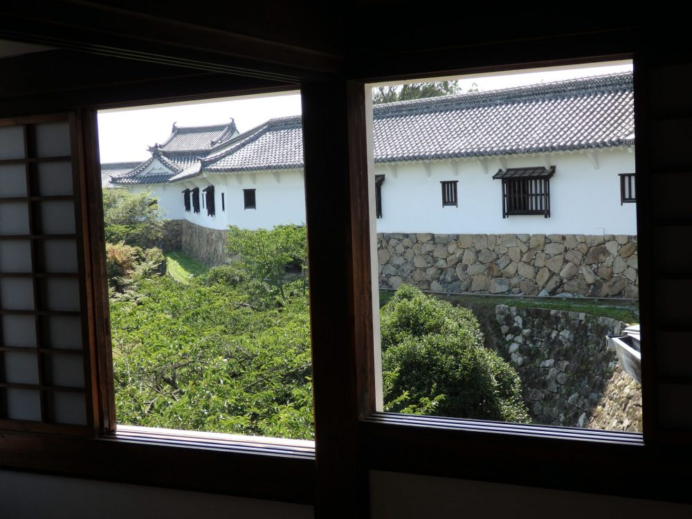 View of the West Bailey from Himeji Castle. A window frames the view, and the baily is only one story tall, white sided, but resting on a brown stone foundation.