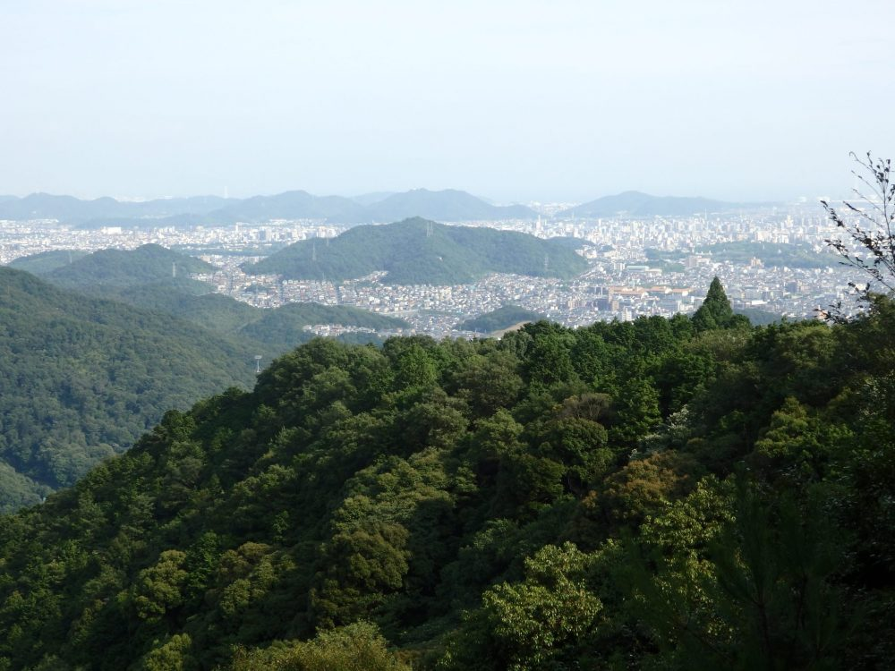 view from the top of the cable car up Mt. Shosha in Himeji: in the near distance is a wooded hill; in the distance the city almost fills the picture.