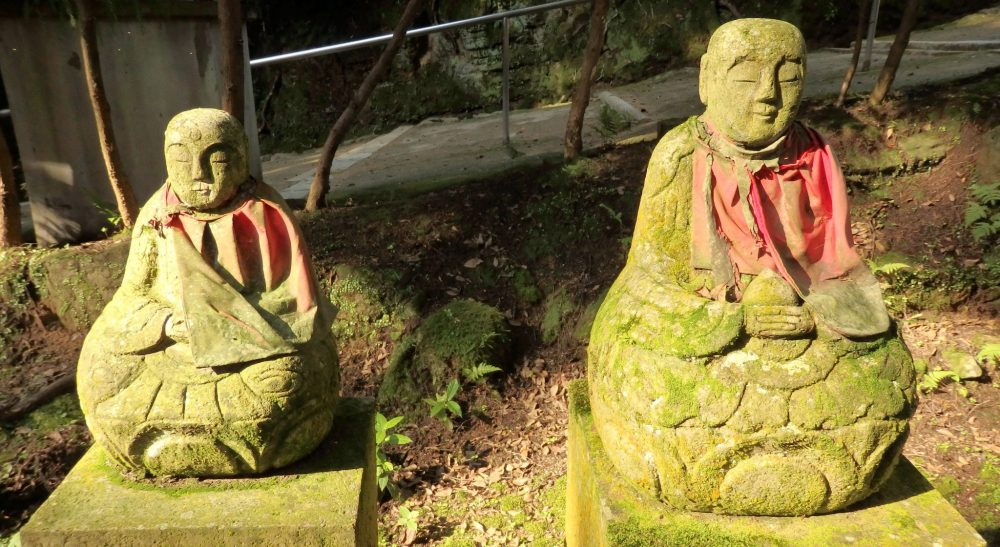 small, simple stone statues in the woods at Engyoji shrine. They are each in a sitting pose and look like monks praying. Each has a faded red cloth tied around its neck.