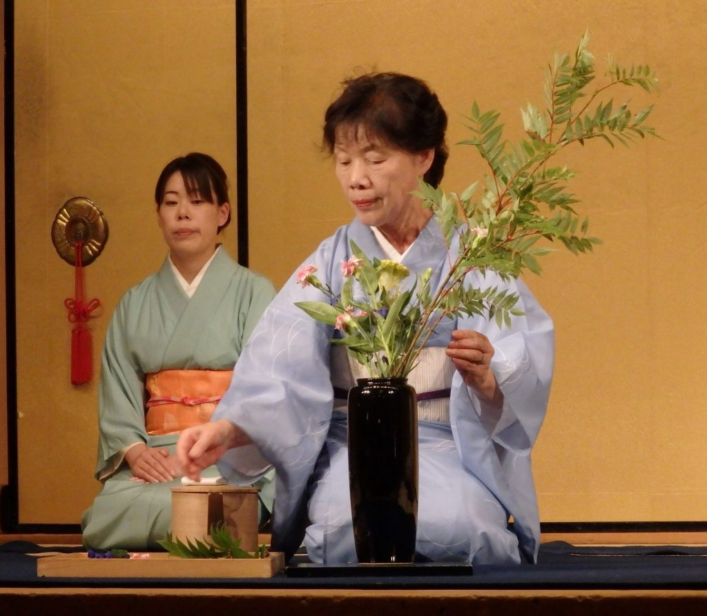 a woman in kimono kneels, arranging leaves and flowers in a vase in front of her on the floor, in Gion Corner