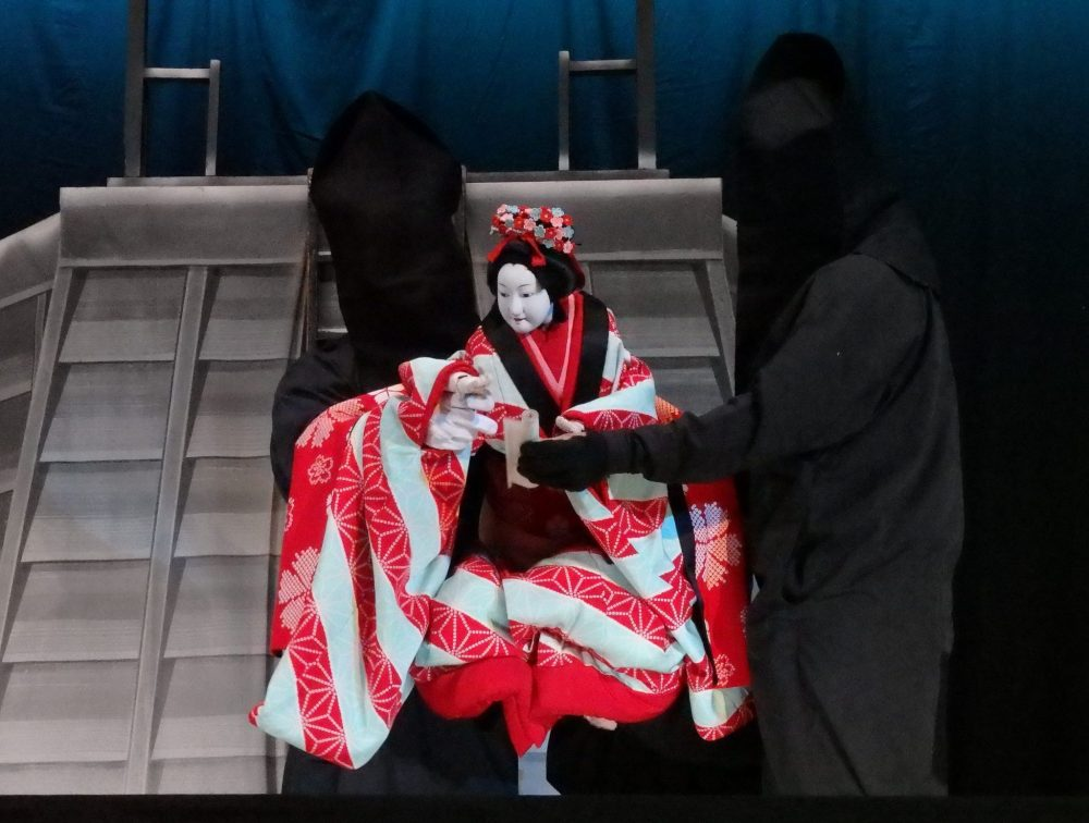 The puppet, dressed in an ornate, flowing, kimono, is carried by two puppeteers: men dressed entirely in black, including hoods over their faces. Gion Corner