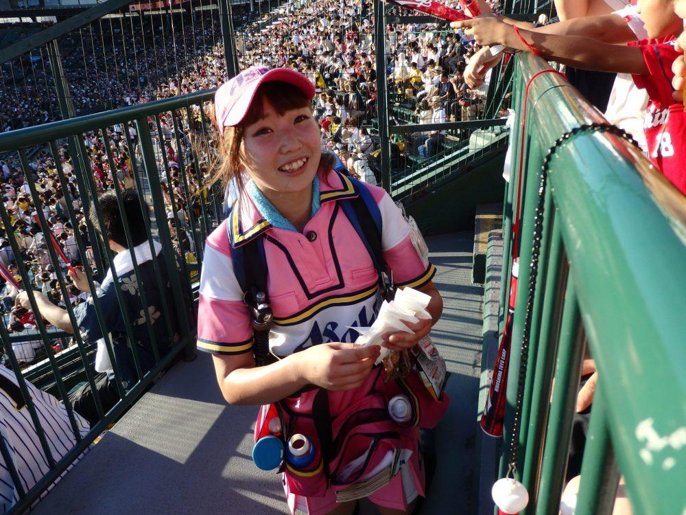a bear hawker selling beer at the baseball game between the Hanshin Tigers and the Hiroshima Carp