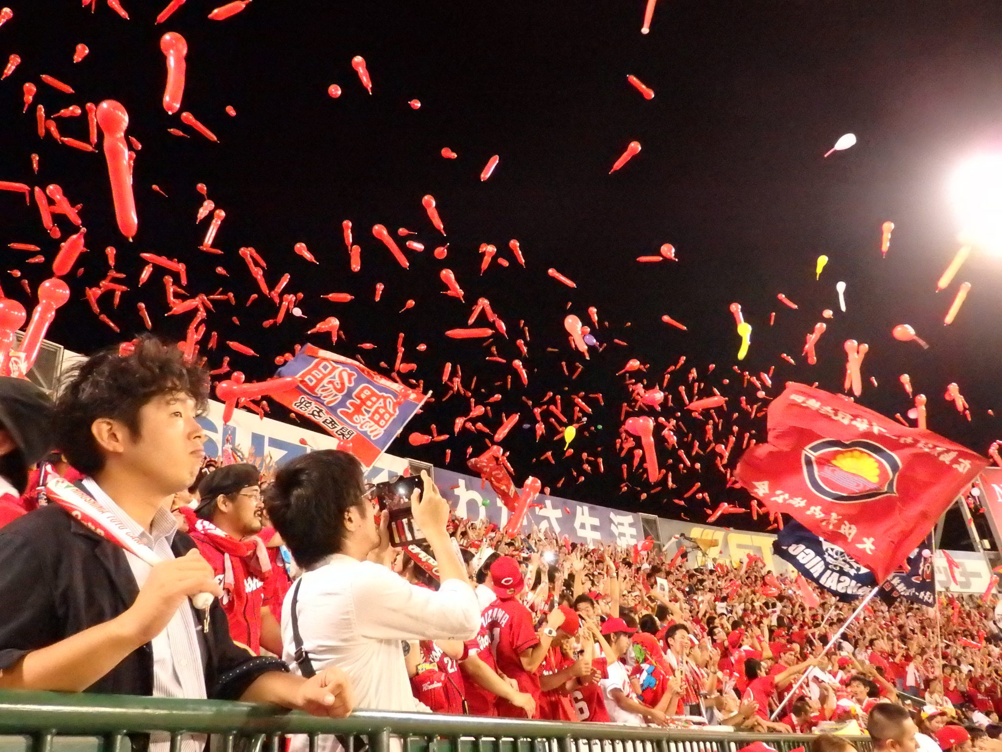 Supporters of the Hiroshima Carp release whistling balloons at the top of the 7th inning.