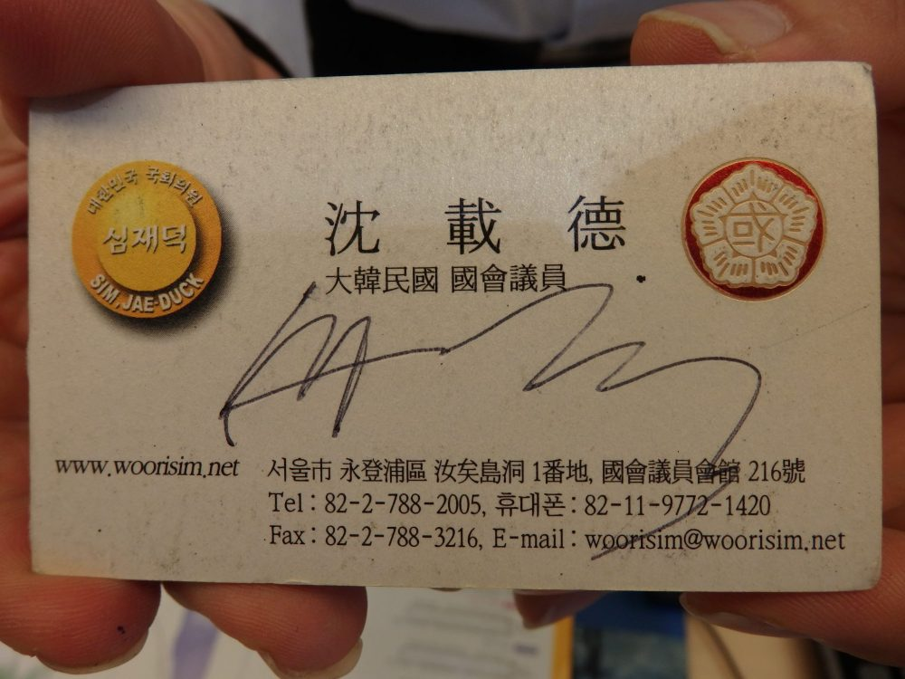 The business card is pretty typical: beige background with the info in black, mostly in Korean, except that Mr. Toilet House's signature is scrawled across the middle. There are two crests or logos, on on either side. The left-hand one is yellow and, besides the Korean lettering also says Sim Jae Duck. The right-hand one is some symbols inside a 5-sided crest.