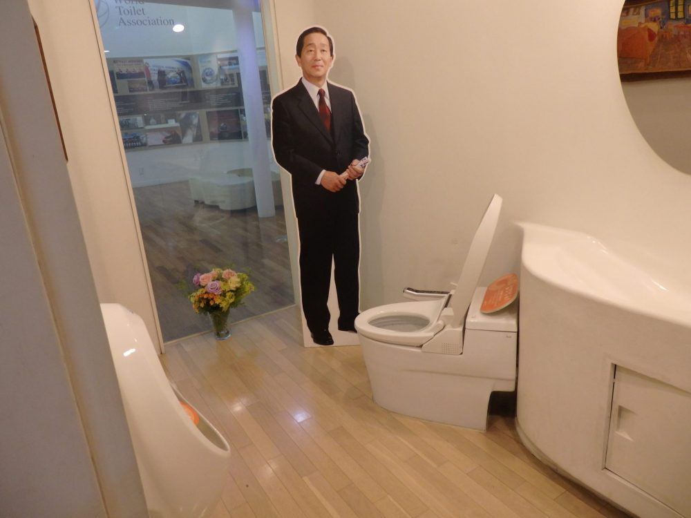The bathroom has a window in the background looking out on what is now exhbit space. A vase of flowers stands on the floor in front of it. The toilet stands on the diagonal, facing the window at a slant. Next to it is a life-size standing image of Mr. Toilet House in a suit and tie. A mirror is partly visible on the right-hand wall and a urinal on the left-hand wall.