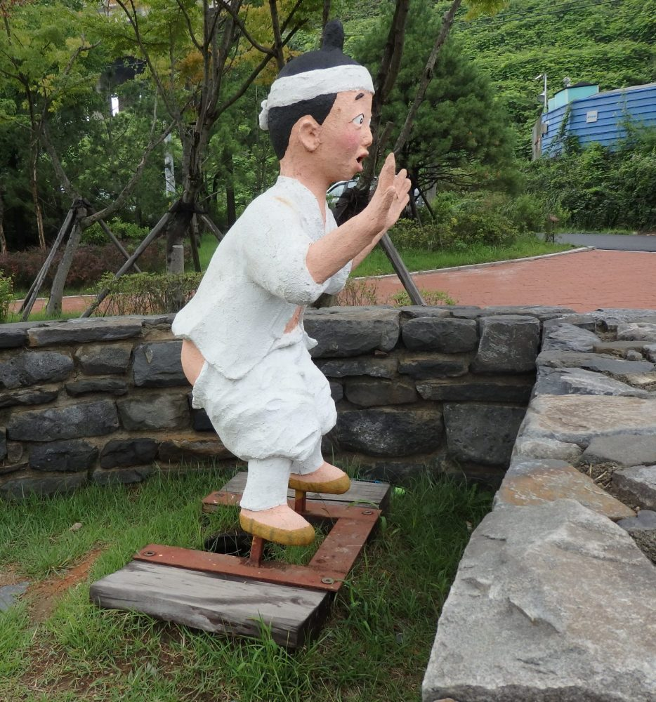 Plaster statue of a Korean peasant slightly squatting, with a surprised look on his face, above two stones. He is wearing a white outfit and has a white headband tied around his head. His pants are pulled down around his thighs and his hands are up in the air as if someone is pointing a gun at him.