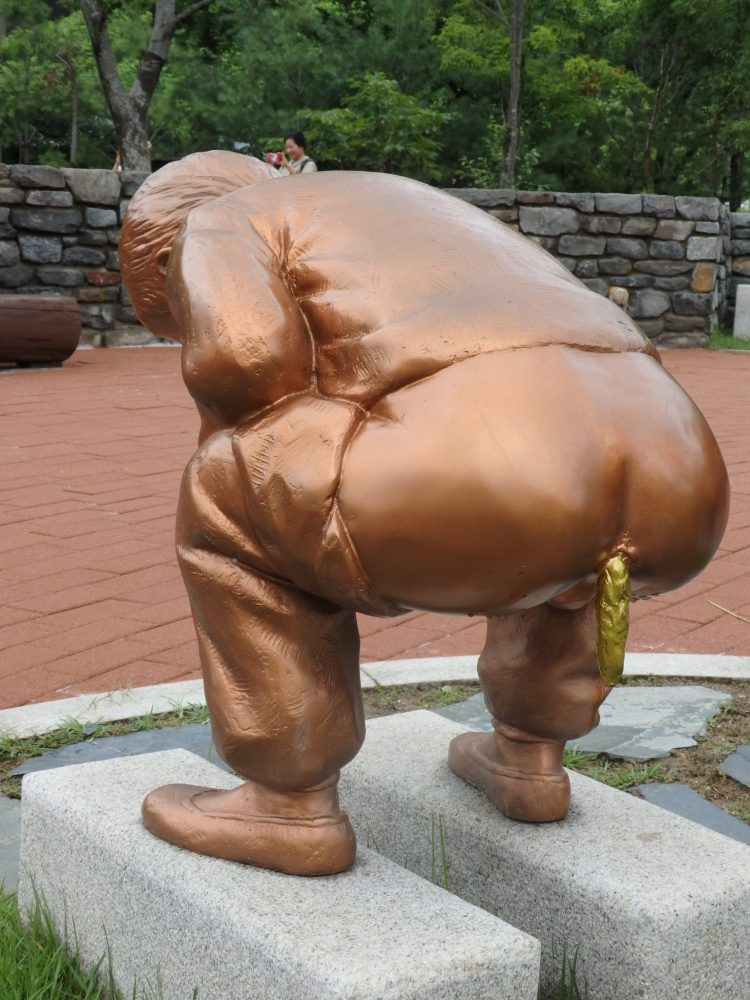 The statue is in a copper color: a figure of a man, standing on a historical toilet consisting of two rectangular slabs of stone. The idea is to stand on the stones and poop/pee between them. In the photo the man is facing away from the camera with his pants pulled down to mid-thigh. He is squatting and a large poop is emerging from his anus, hanging down. The poop is for some reason, gold-colored.