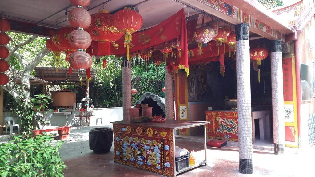 shrine with colorful lanterns and paintings decorating the altar, on Pulau Ubin