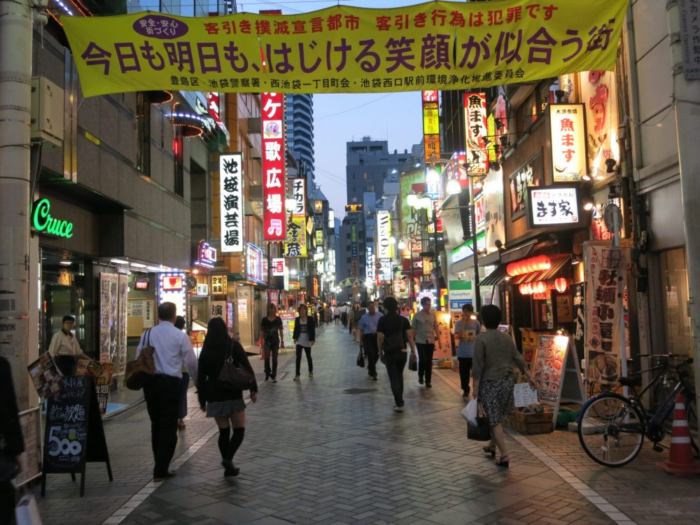 A street around the corner from where I stayed in Tokyo, at dinnertime. The buildings on either side are covered with lighted signs trying to catch the attention of passersby.