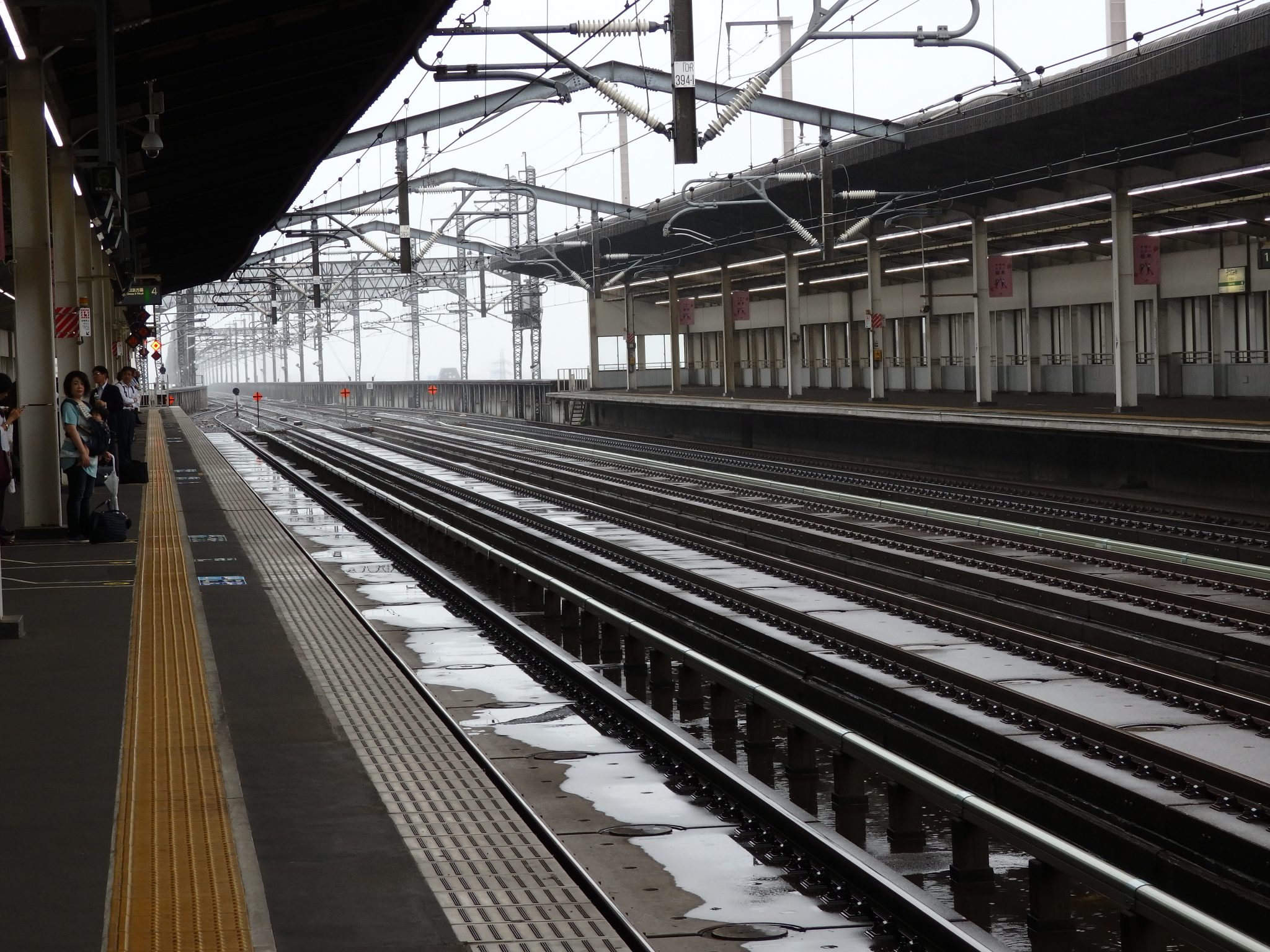A view in a Japanese railway station looking down the tracks, no trains in sight.