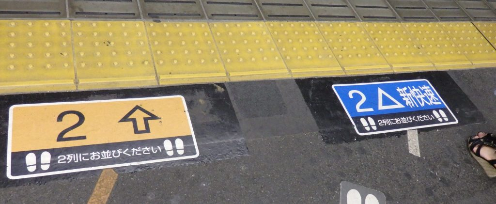 signs on the floor of the platform indicate where to wait