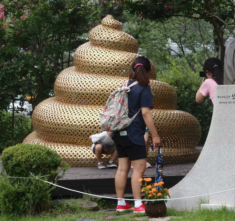 The turd is about two meters high, a neat pyramid, made from some kind of gold-colored plastic or metal mesh. Two adult women stand with their backs to the camera, looking at two children at the base of the turd, who are partly obscured by one of the women. Enough is visible of one of the children to see that he/she is squatting as if pooping.
