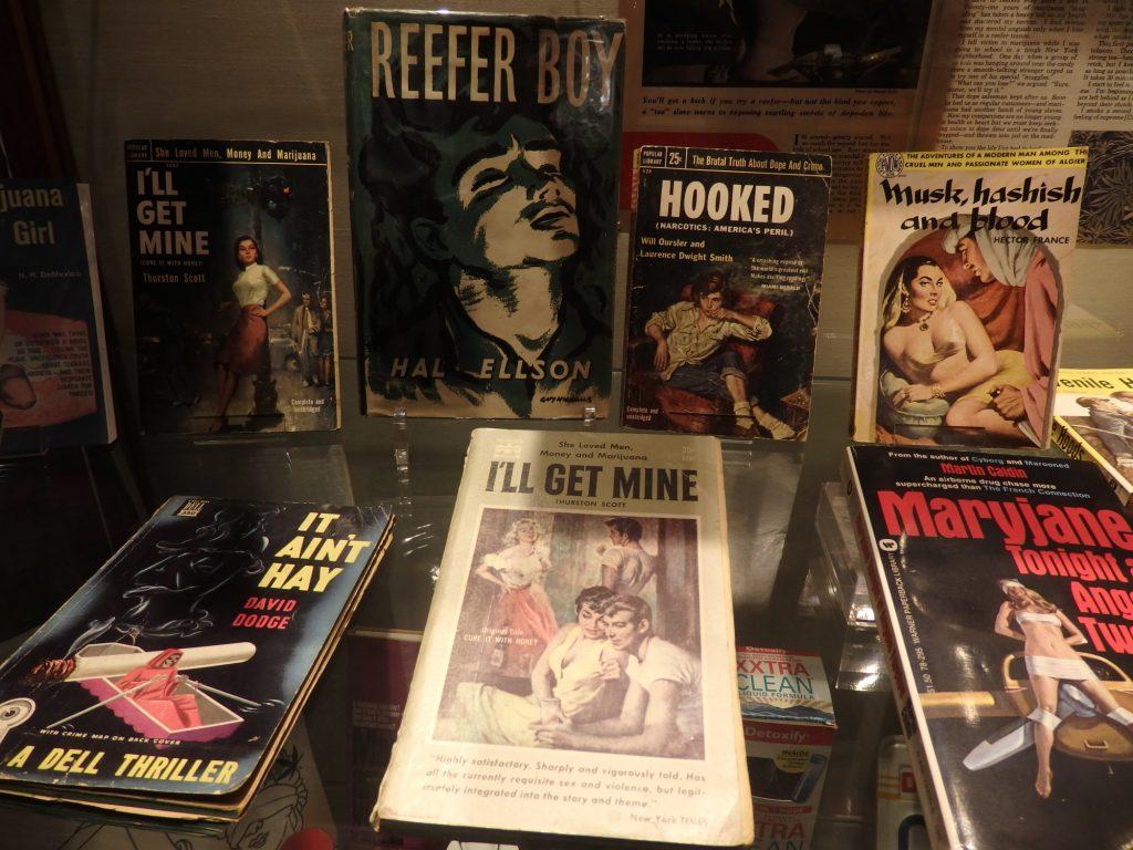 miscellaneous books about marijuana in a glass case at the hash, marijuana & hemp museum in Amsterdam