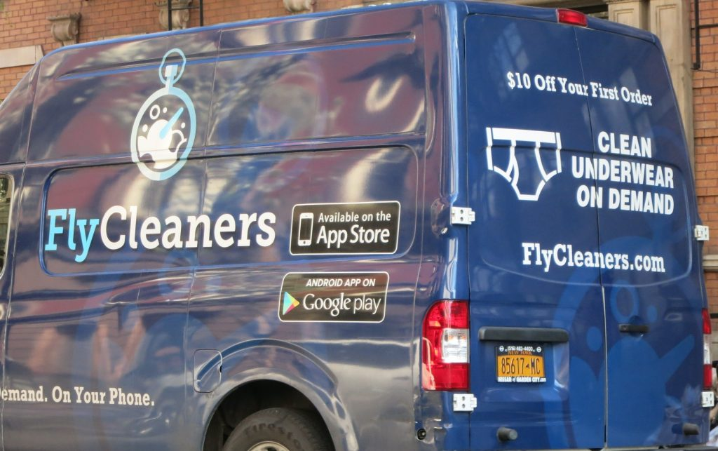 "a van with the text ""FlyCleaners"" and ""Clean Underwear on Demand"" in New York City"